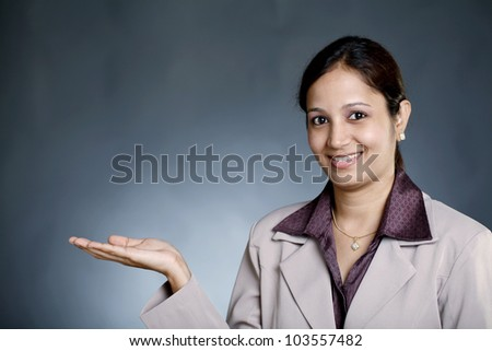 Young happy business  woman holding her hand palm up - stock photo