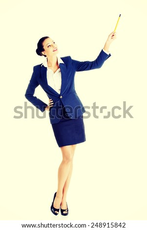 Young happy business woman pointing up with pen.