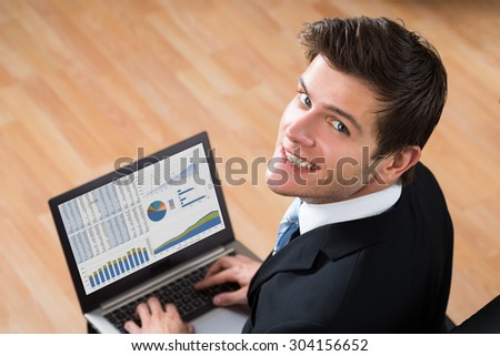 Young Happy Businessman Analyzing Statistical Data On Laptop In Office - stock photo
