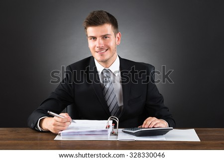 Young Happy Businessman Checking Invoice With Calculator At Desk