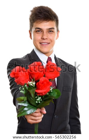 Young happy businessman smiling while giving red roses ready for Valentine's day