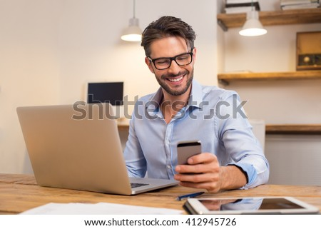 Young happy businessman smiling while reading his smartphone. Portrait of smiling business man reading message with smartphone in office. Man working at his desk at office.