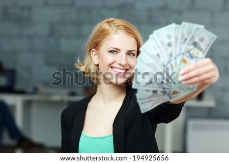 Young happy businesswoman holding bills of dollars in office - stock photo