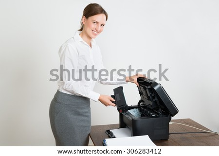 Young Happy Businesswoman Holding Laser Cartridge With Printer At Desk - stock photo