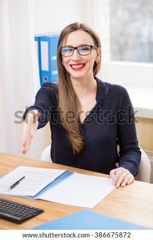 Young happy businesswoman in glasses meeting partner for negotiations in her office