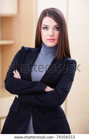 Young happy businesswoman in office with crossed arms