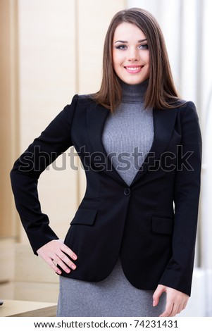 Young happy businesswoman in office with crossed arms - stock photo