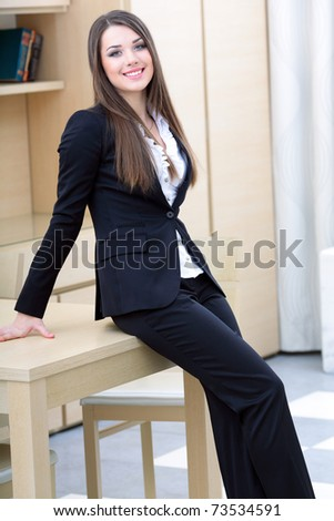 Young happy businesswoman in suit standing near the table in the office - stock photo