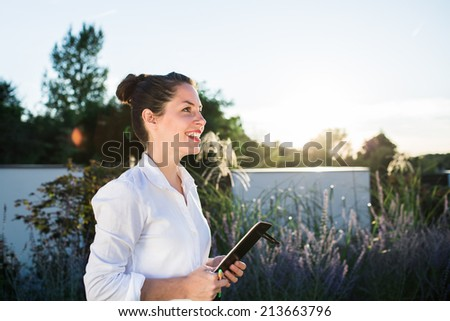 Young happy businesswoman or landscape architect in white shirt speaking with her client in the dark background with trees, bushes and the garden fence. Strong sunset backlit. - stock photo