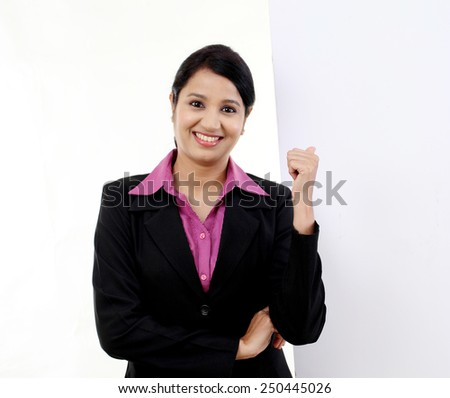 Young happy businesswoman showing blank signboard - stock photo