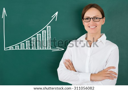 Young Happy Businesswoman Standing In Front Of Graph Drawn On Green Chalkboard