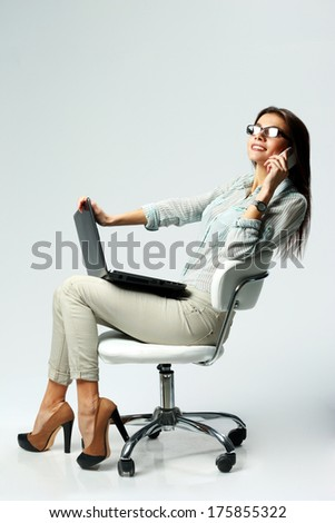 Young happy businesswoman using laptop and phone on gray background - stock photo