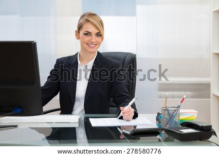 Young Happy Businesswoman Working At Desk In Office - stock photo