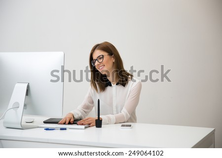 Young happy businesswoman working in office - stock photo