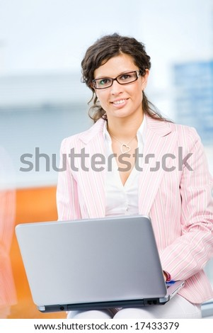 Young happy businesswoman working on laptop computer in fron front of office window, smiling. - stock photo