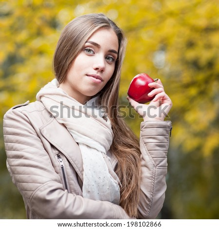 young happy casual caucasian woman in autumn park smiling while holding red apple - stock photo