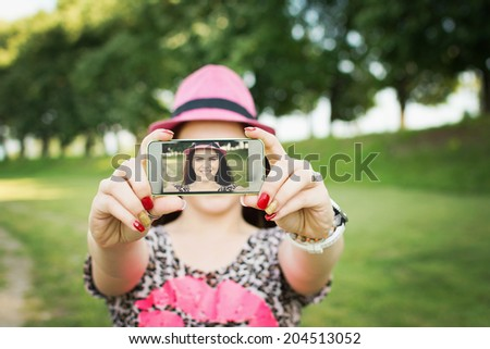 Young happy Caucasian brunette woman with pink hat and animal print shirt taking a selfie with smart phone in nature. Beautiful Caucasian girl posing for a self portrait outdoors in park in summer. - stock photo