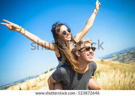 Young happy caucasian couple in love walking and having fan at mountain during summer