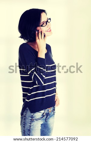 Young happy caucasian woman is calling with a mobile phone (smartphone) isolated on white - stock photo