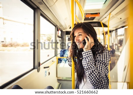Young happy caucasian woman wearing casual clothes is calling with her smartphone on the bus