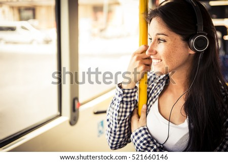 Young happy caucasian woman wearing smart casual clothes is listening music on the bus with some modern headphone