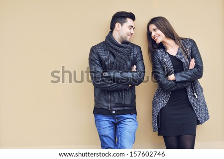 Young happy cheerful couple standing near a wall and looking to each other - stock photo
