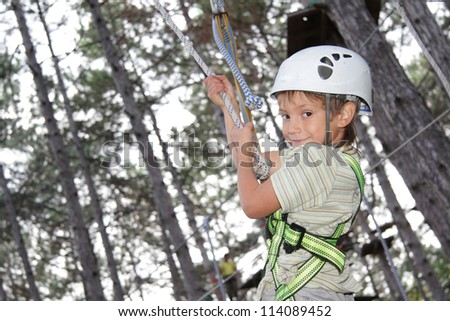 young happy child boy in adventure park wearing mountain helmet and safety equipment - stock photo