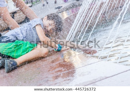 young happy child boy playing with water fountain, outdoor portrait