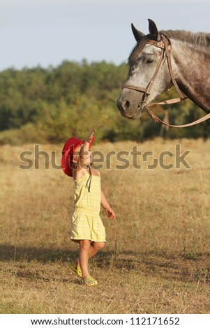 young happy child girl and horse on natural background - stock photo