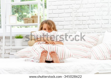 young happy child girl in bed at home, indoor portrait - stock photo