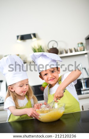 young happy children kids family having fun preparing a cake in kitchen at home - stock photo