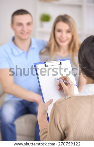 Young happy couple after therapy session with family psychologist. Focus on psychologist. - stock photo