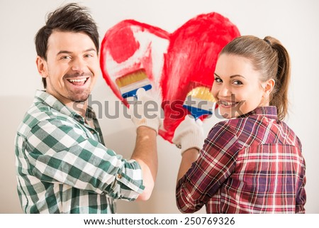 Young happy couple are painting a heart on the wall while doing repair at home. - stock photo