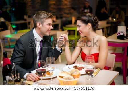 Young happy couple at the restaurant - stock photo