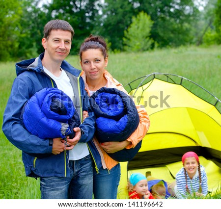 Young happy couple camping near tent in park - stock photo
