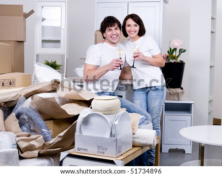 Young happy couple celebrating new home together with glass of champagne - indoors - stock photo