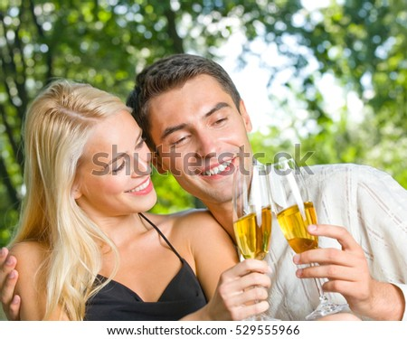 Young happy couple celebrating with champagne, outdoors. Love, flirt, romantic, relations theme concept.
