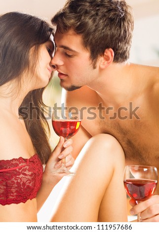 Young happy couple celebrating with red wine at bedroom