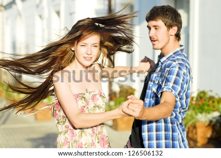 Young happy couple dancing on street in the summer outdoors - stock photo