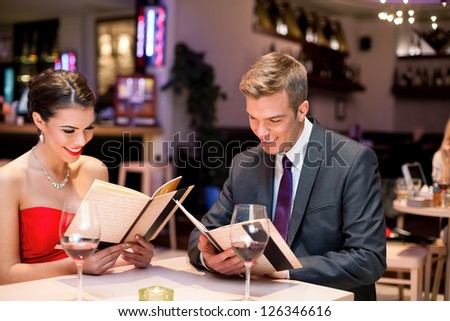 young happy couple dining out in restaurant and reading menu - stock photo