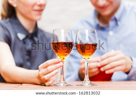 Young happy couple drinking wine in a restaurant - stock photo