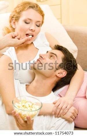 Young happy couple eating popcorn together at home - stock photo