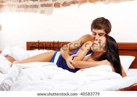 Young happy couple embracing in a bed - stock photo