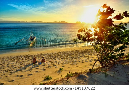 Young happy couple enjoying a beautiful sunset on the beach island of El Nido - stock photo