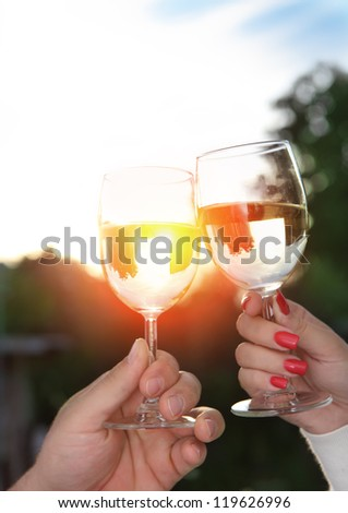 Young happy couple enjoying a glasses of white wine in the garden - stock photo
