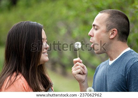 Young happy couple enjoying each others company outdoors.  The man is blowing a dandelion into the face of his girlfriend wife or fiance. - stock photo