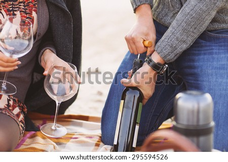 Young happy couple enjoying picnic on the beach together. Man opening bottle of wine. Close up - stock photo