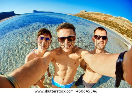 young happy couple friends on the beach taking selfie on sea background. Balos beach, Crete, Greece. - stock photo
