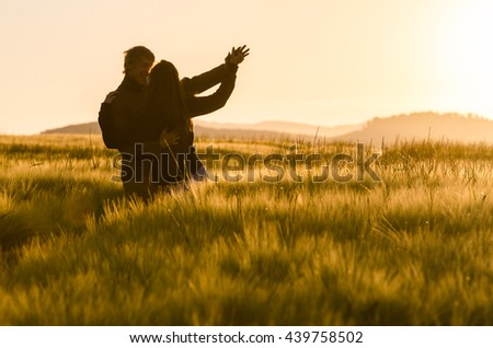 Young, happy couple have a piggy back in the wheat field.Summer sunrise outside - stock photo