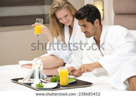 Young happy couple having breakfast in luxury hotel room - stock photo